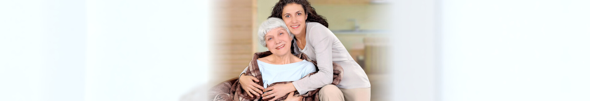female caregiver hugging senior woman while sitting