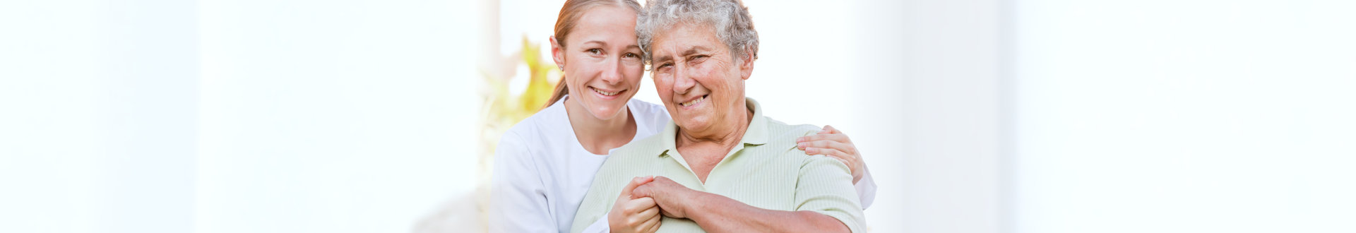 beautiful caregiver with senior woman smiling